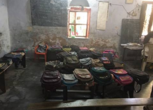 Classroom in India filled with benches and backpacks.