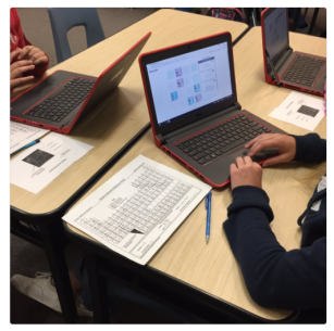 Students referencing a periodic table while playing the Desmos Polygraph: Periodic Table